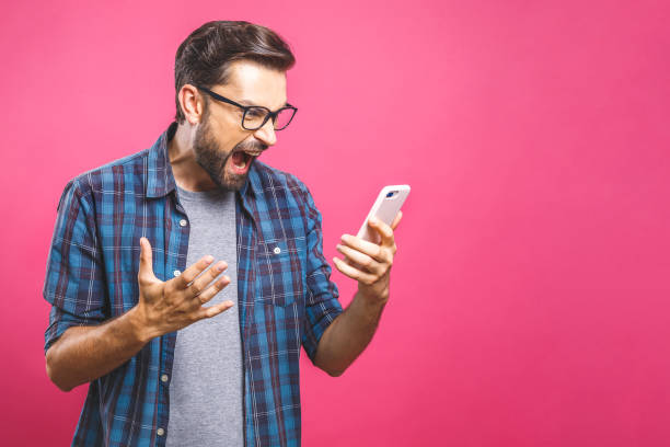 Young caucasian man angry, frustrated and furious with his phone, angry with customer service over pink background. Young caucasian man angry, frustrated and furious with his phone, angry with customer service over pink background. agitation stock pictures, royalty-free photos & images