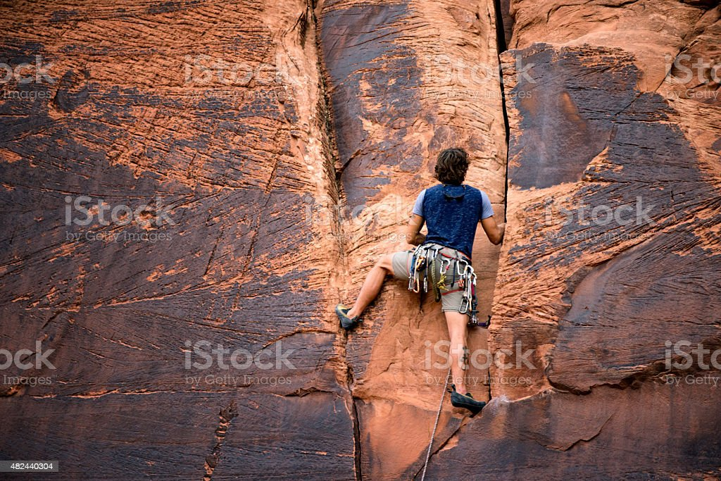 Young Caucasian Man Climbing a Sheer Cliff of Red Sandstone stock photo