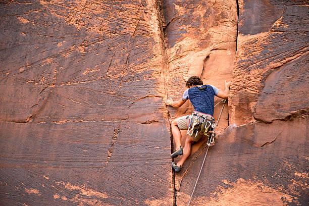 young caucasian man climbing a sheer cliff of red sandstone - moab utah stockfoto's en -beelden