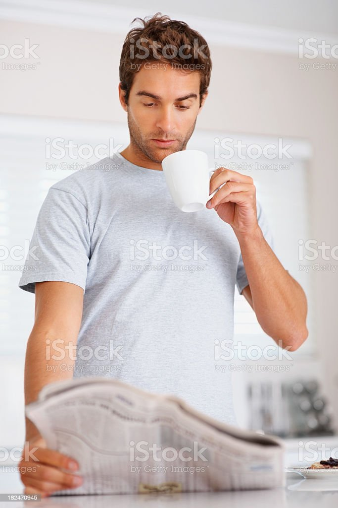 Young Caucasian man drinking coffee while reading newspaper royalty-free stock photo