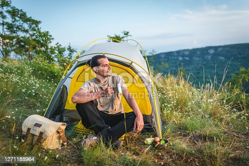 Young caucasian man enjoying the sunset outside his tent drinking hot tea. Outdoor camping leisure activity concept.