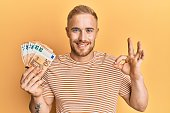 Young caucasian man holding bunch of 50 euro banknotes doing ok sign with fingers, smiling friendly gesturing excellent symbol
