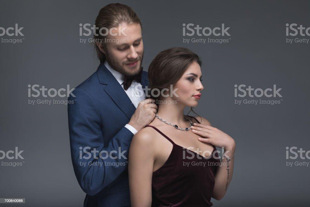 kaukasischen Jüngling im Smoking, seine Freundin Halskette aufsetzen Lizenzfreies stock-foto