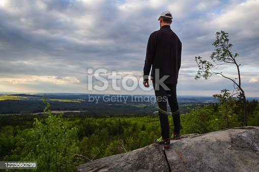 Young caucasian man in white cap standing on rock and looking to valley. Czech republic