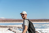 Young caucasian man wearing sunglasses and cap looking at camera with lagunas Escondidas (hidden gems) of Baltinache one of the secret spots of Atacama Desert, Chile, South America