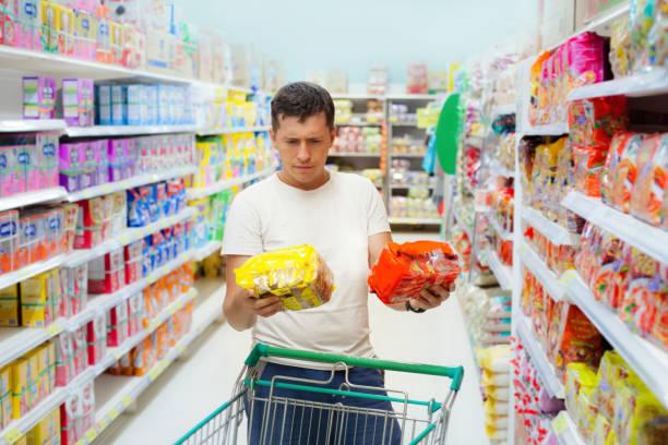 Jovem homem caucasiano faça escolher entre dois produtos semelhantes. - foto de acervo