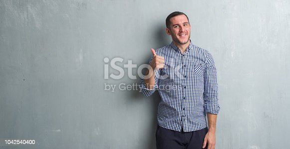 istock Young caucasian man over grey grunge wall doing happy thumbs up gesture with hand. Approving expression looking at the camera with showing success. 1042540400