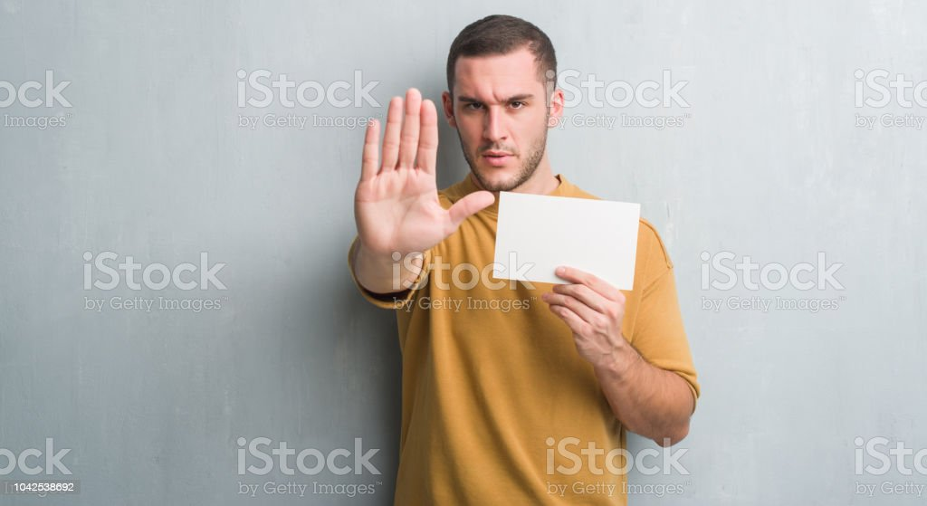 Young caucasian man over grey grunge wall holding blank card with open hand doing stop sign with serious and confident expression, defense gesture stock photo