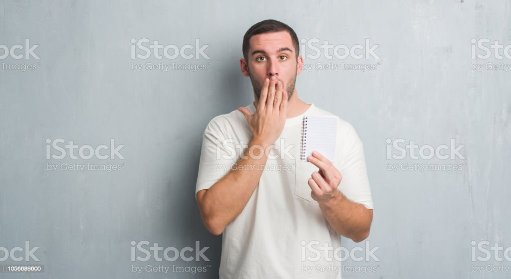 Young caucasian man over grey grunge wall showing notebook cover mouth with hand shocked with shame for mistake, expression of fear, scared in silence, secret concept stock photo
