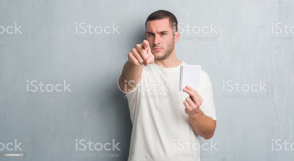 Young caucasian man over grey grunge wall showing notebook pointing with finger to the camera and to you, hand sign, positive and confident gesture from the front stock photo