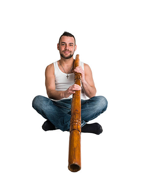 young caucasian man play music on his didgeridoo - didgeridoo stock photos and pictures