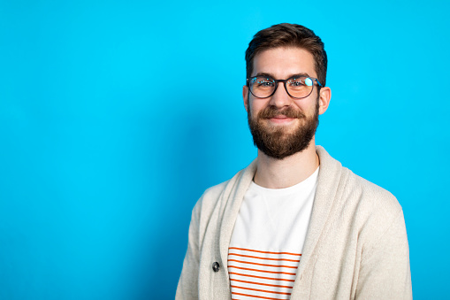 Studio portrait of a young man posing against blue background.