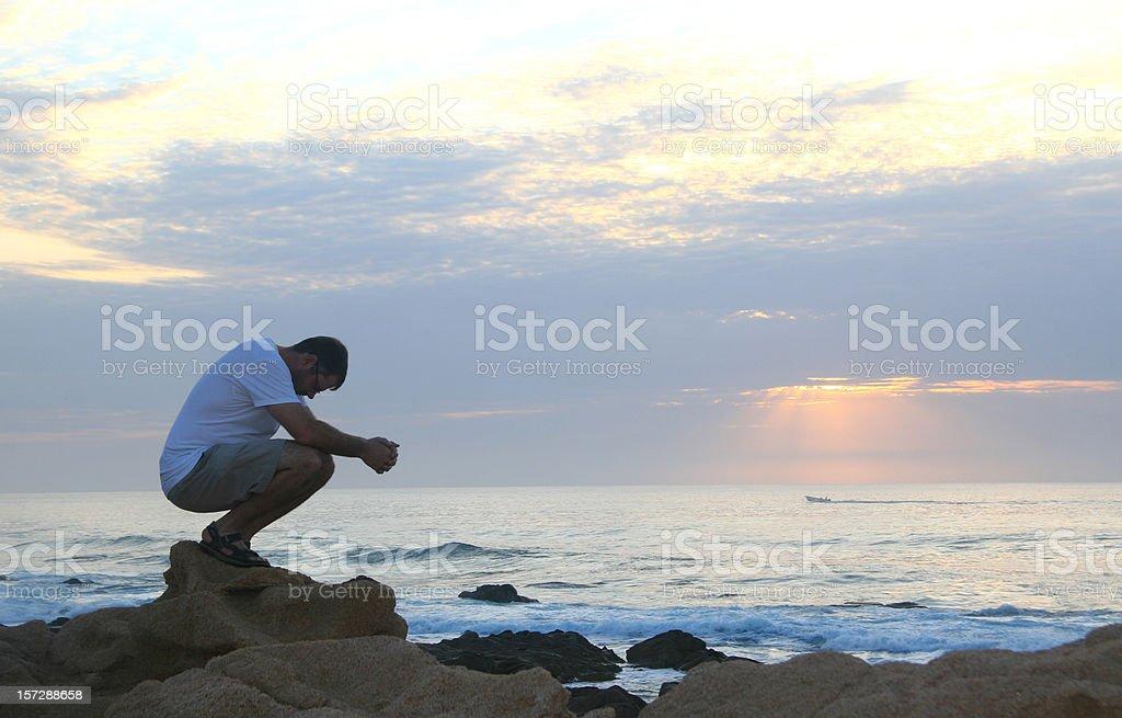 Young Caucasian Man Praying Beside Ocean stock photo
