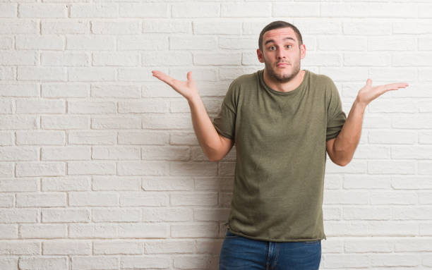 Young caucasian man standing over white brick wall clueless and confused expression with arms and hands raised. Doubt concept. Young caucasian man standing over white brick wall clueless and confused expression with arms and hands raised. Doubt concept. shrugging stock pictures, royalty-free photos & images