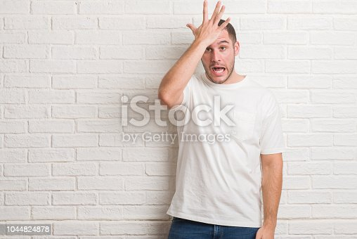 1046559700istockphoto Young caucasian man standing over white brick wall surprised with hand on head for mistake, remember error. Forgot, bad memory concept. 1044824878