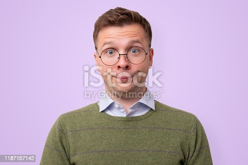 Young caucasian man student in funny glasses looking confused. Studio shot