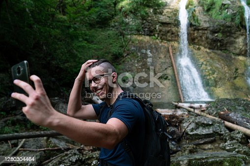 Young Caucasian man taking a selfie in the nature