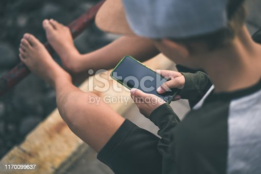 Young caucasian man using smartphone to share pictures online with remote friends. Barefoot teen watching social video with cell phone sitting near the sea. Trendy boy texting with new smart device.