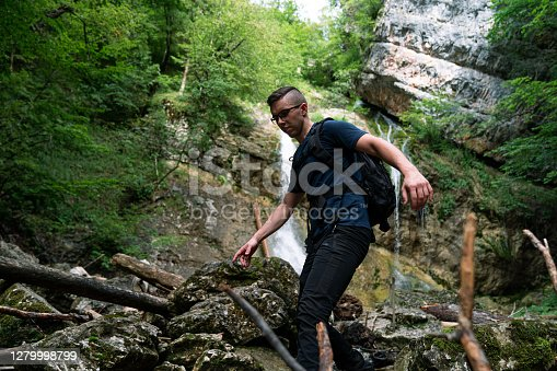 Young Caucasian man walking over rocks and branches