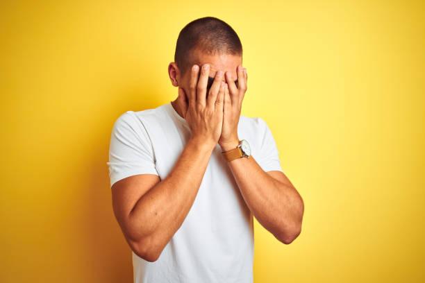 joven caucásico con camiseta blanca casual sobre fondo aislado amarillo con expresión triste cubriendo la cara con las manos mientras llora. concepto de depresión. - vergüenza fotografías e imágenes de stock