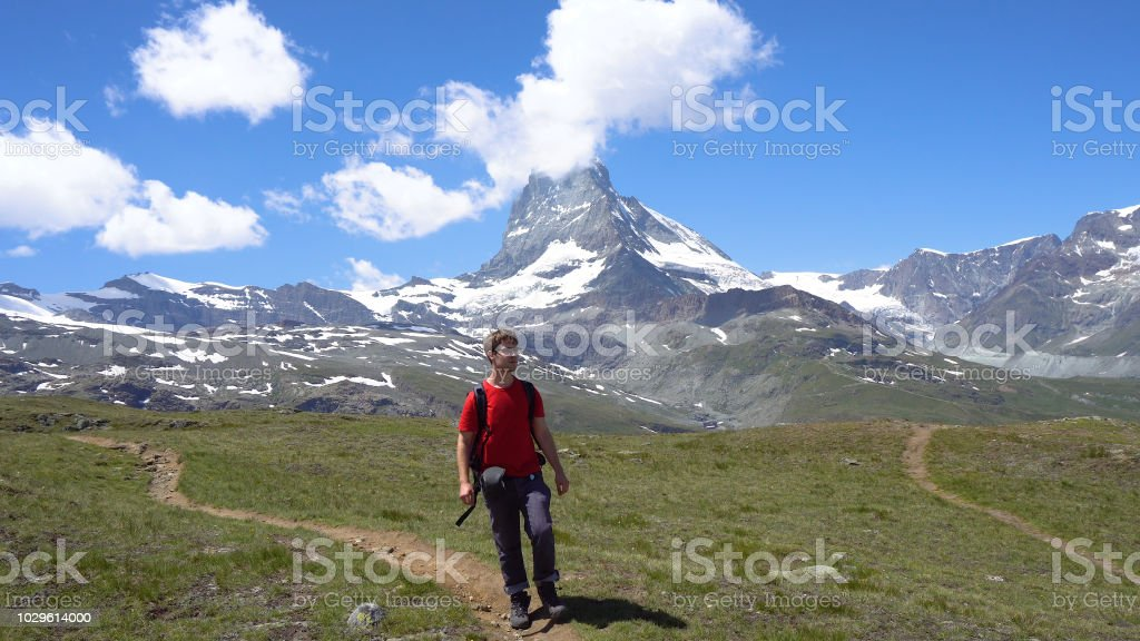 Young Caucasian Man With Backpack Hiking in Mountains stock photo