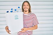 Young caucasian man with blond long hair and beard recycling plastic bottles