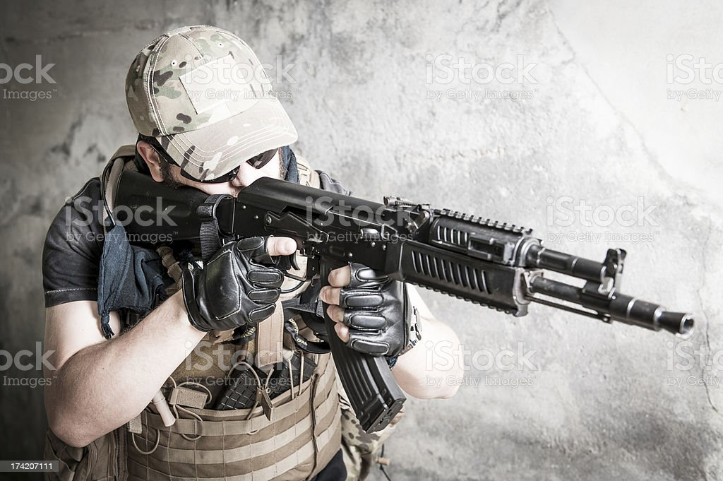 Young Caucasian Modern Contractor Soldier Taking Aim with Assault Rifle stock photo