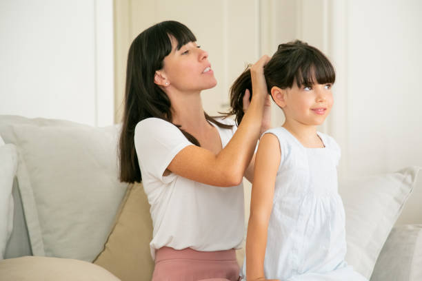 Young Caucasian mother holding hairs of her daughter stock photo