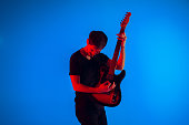 Young and joyful caucasian musician playing guitar on gradient blue studio background in neon light. Concept of music, hobby, festival. Colorful portrait of modern artist. Emotional and inspired.