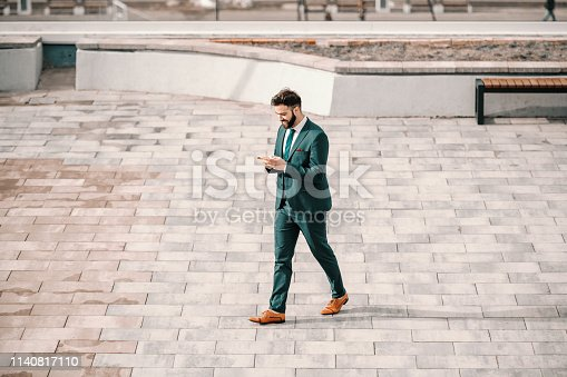Young Caucasian perspective Caucasian businessman in formal wear walking on the street and using smart phone. A goal is a dream with a deadline.