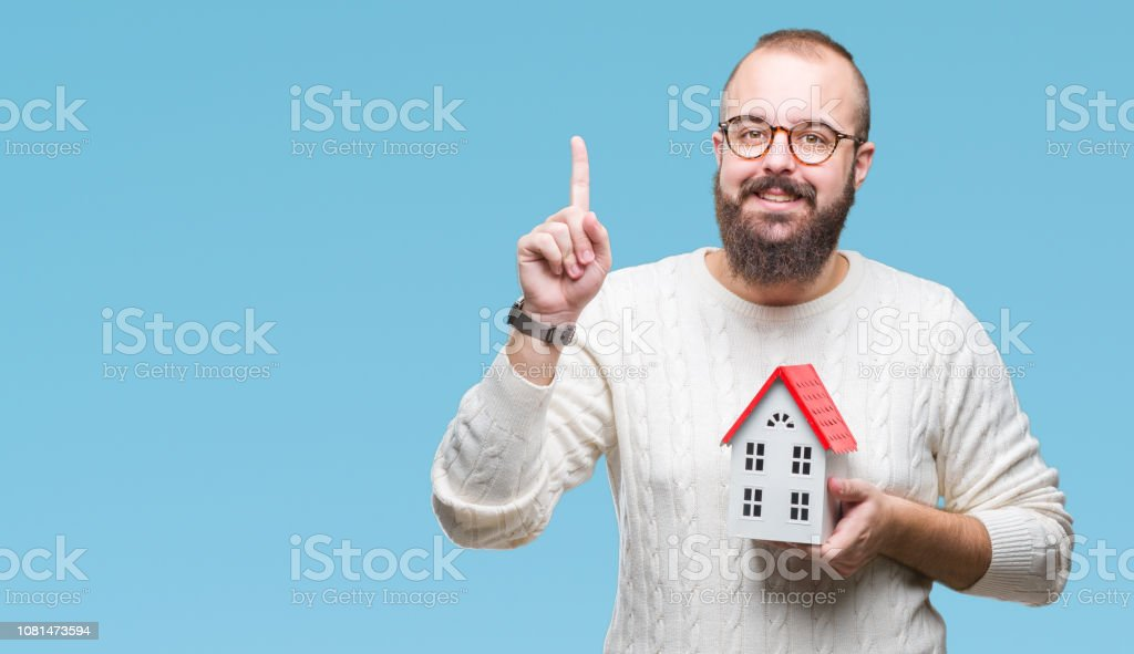 Young caucasian real state agent man holding house isolated...