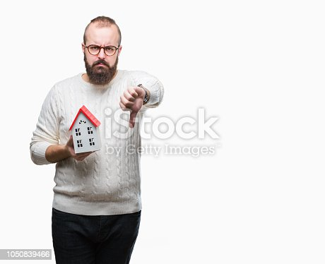 Young caucasian real state agent man holding house isolated background with angry face, negative sign showing dislike with thumbs down, rejection concept