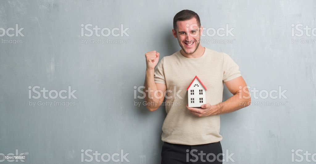 Young caucasian real state agent man over grey grunge wall holding...