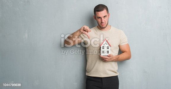 Young caucasian real state agent man over grey grunge wall holding house with angry face, negative sign showing dislike with thumbs down, rejection concept