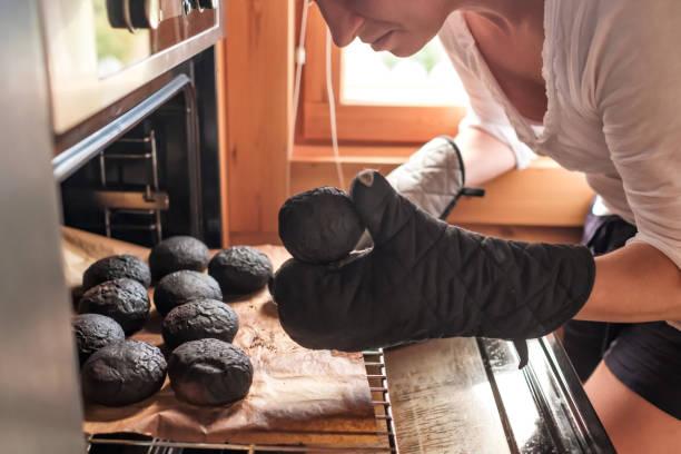 young caucasian sad woman taking burnt bread - burned oven imagens e fotografias de stock