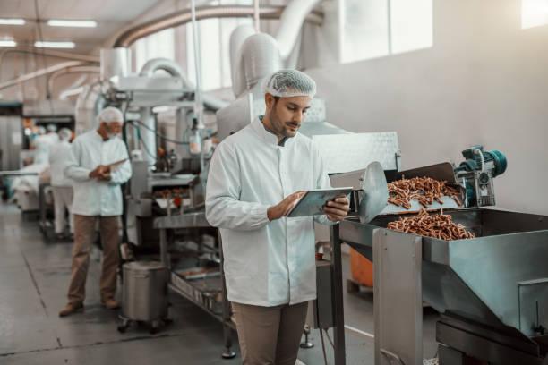 unga kaukasiska allvarliga handledare utvärdera kvaliteten på livsmedel i livsmedelsverket medan du håller tabletten. man är klädd i vit uniform och har hårnät. - livsmedelstillverkningsfabrik bildbanksfoton och bilder