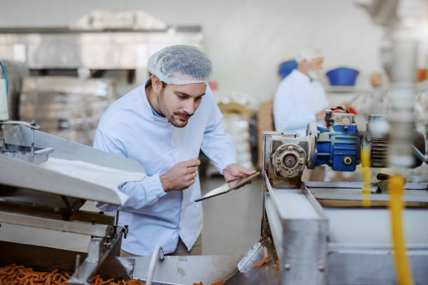 Young Caucasian serious supervisor evaluating quality of food in food plant while holding tablet. Man is dressed in white uniform and having hair net. Young Caucasian serious supervisor evaluating quality of food in food plant while holding tablet. Man is dressed in white uniform and having hair net. hair net stock pictures, royalty-free photos & images