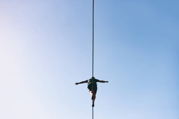 Young Caucasian slackline man practicing slackline against the sky on a clear summer day stock photo
