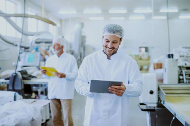 unga kaukasiska leende handledare i steril vit uniform med hjälp av tablett medan du står i mat fabrik. i bakgrund äldre en arbetare som kontrollerar bearbeta med maskin. - livsmedelstillverkningsfabrik bildbanksfoton och bilder