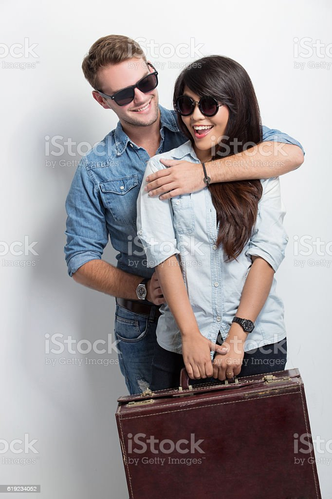 Young caucasian smiling while giving his asian girlfriend a back stock photo