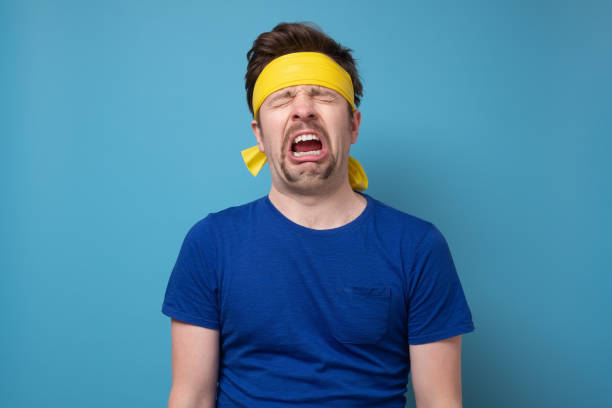 Young caucasian sport man with yellow rubber band whining and crying stock photo