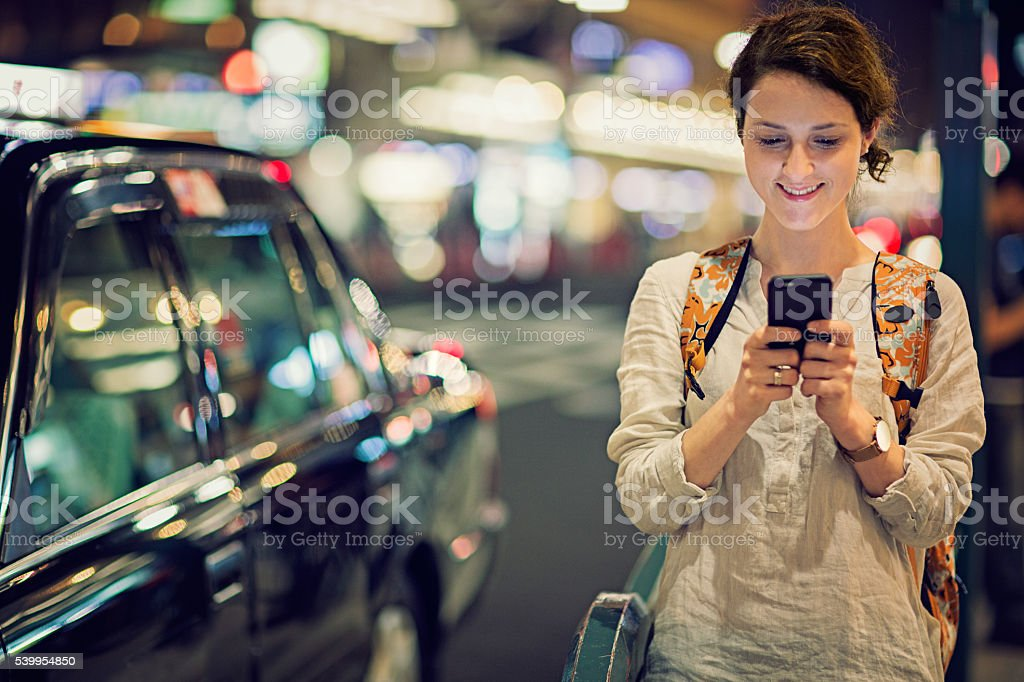 Young Caucasian tourist girl is texting stock photo