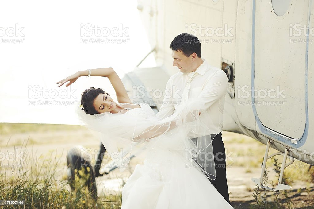 young caucasian wedding couple next to airplane royalty-free stock photo