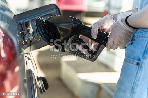 Young woman refueling a car at the gas station. She wearing protective latex gloved to prevent spreading infection because of COVID-19 coronavirus outbreak.