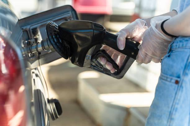 Junge Kaukasierin Weiß langhaarige Frau tankt ein Auto an der Tankstelle. Nahaufnahme ihrer Hand. Sie trug wegen der Coronavirus-Pandemie schützende Latexhandschuhe. – Foto