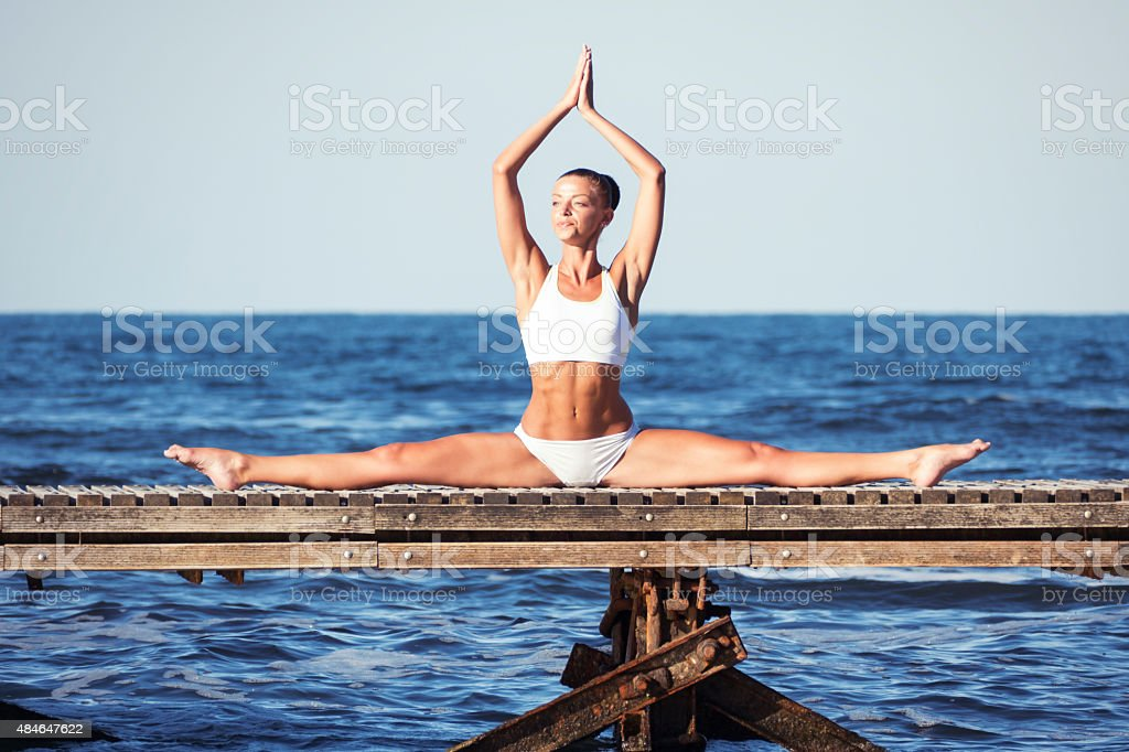 Young caucasian white woman doing yoga on the quay stock photo