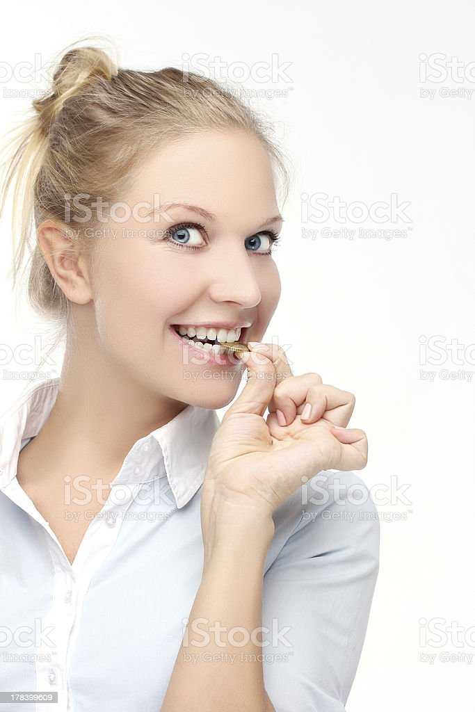 Young caucasian woman biting one euro coin royalty-free stock photo