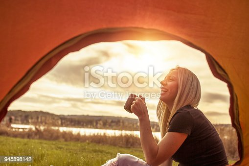 Young caucasian woman drinking coffee in front of tent