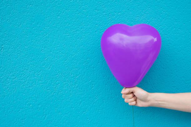 Kaukasische Mädchen Mädchen hält in Hand Purpurrotes Herz geformt Luftballon auf Türkis gestrichenen Wand Hintergrund. Liebe Liebe Spende Kinder romantisches Konzept. Lebendige Farben. Urbane Atmosphäre – Foto