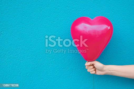 istock Young caucasian woman girl holds in stretched hand bright pink heart shape air balloon on turquoise painted wall background. Valentine love charity donation concept. Vivid Colors. Urban Atmosphere 1089776206